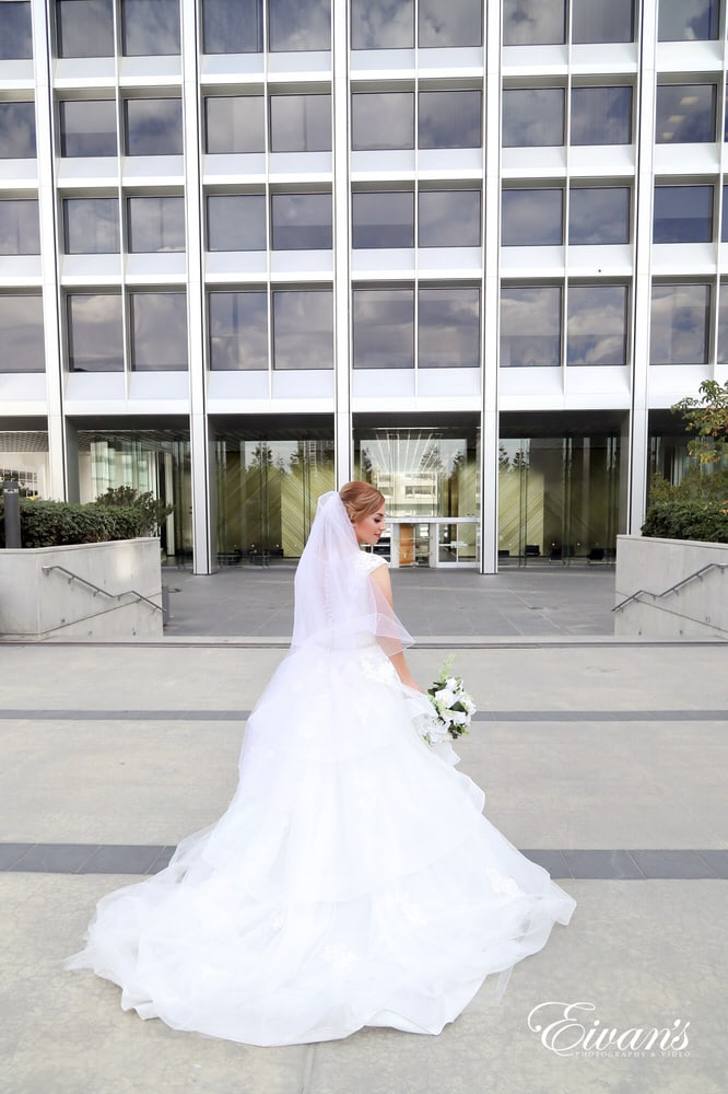 The bride looks absolutely gorgeous standing so perfectly in front of a modern styled building.