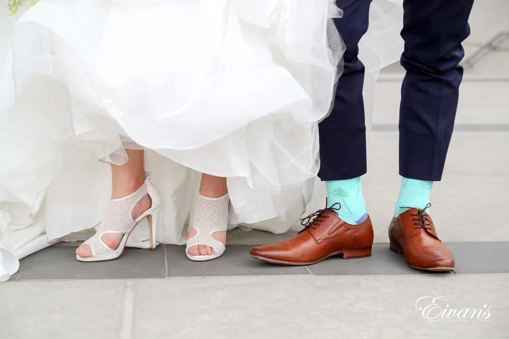 The bride and groom show off their shoes within their perfect wedding day look.