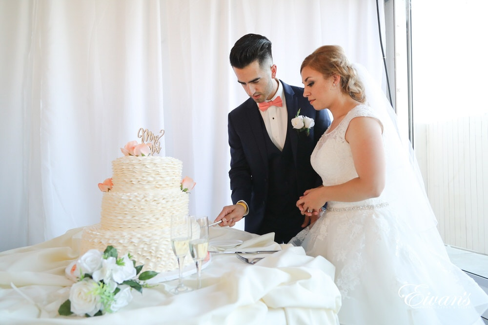The couple cut their stunning and pearly white wedding cake together.