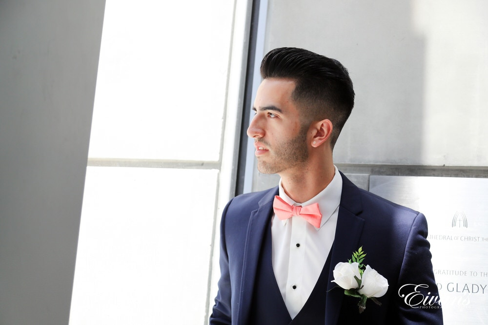 The groom looks out the window longingly waiting to marry the love of his life.