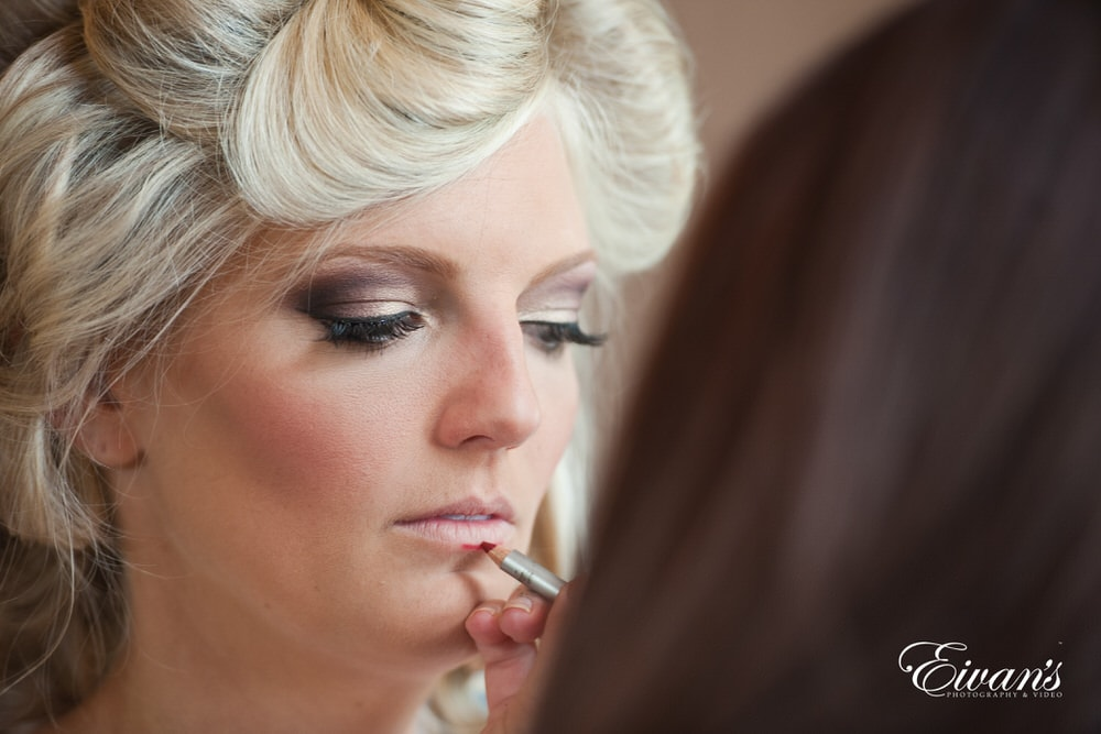 The bride is having her glamorous makeup done for her perfect day.