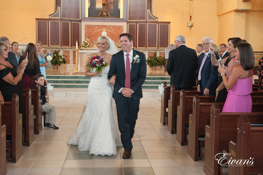 The bride and groom smile ear-to-ear while they leave their ceremony happier than ever.