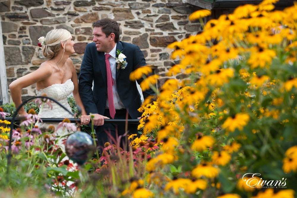 The couple stand together laughing and smiling next to beautiful array of vibrant yellow flowers.