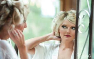 The bride looks at her stunning makeup while waiting for her hair to curl perfectly.