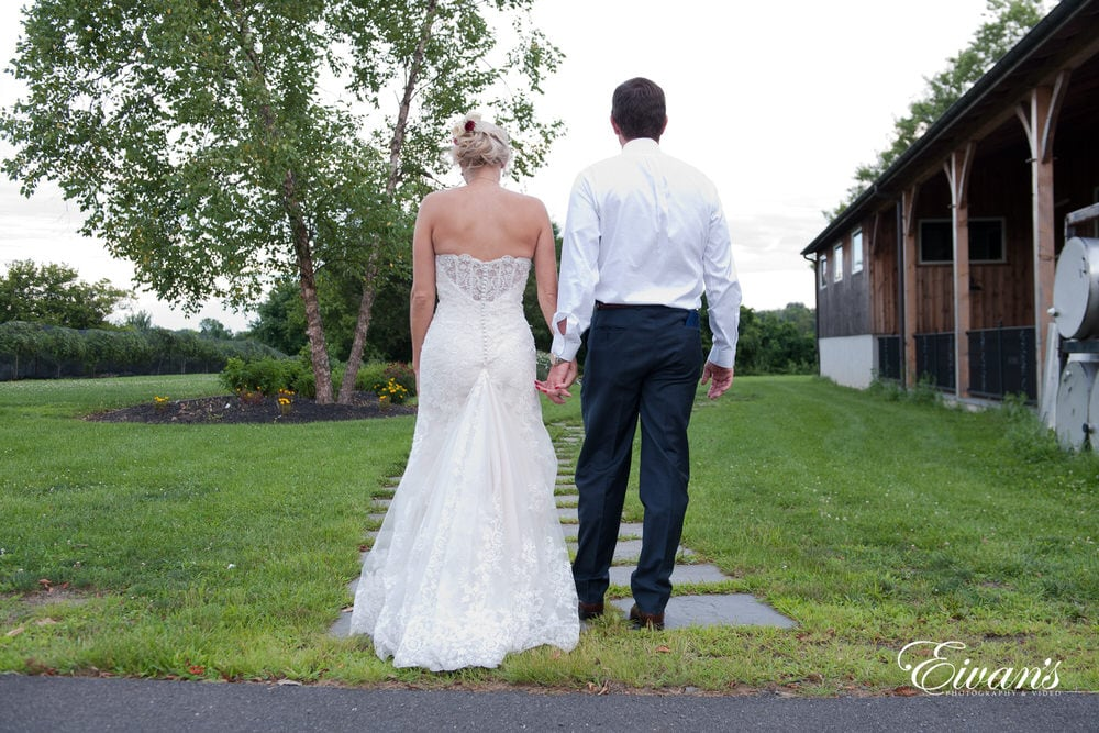 The couple walk hand-in-hand together down a gorgeous stone pathway to a mysterious getaway.