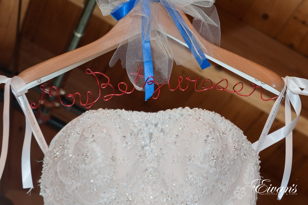On the bride's hanger is her new soon-to-be last name with her stunning wedding gown.