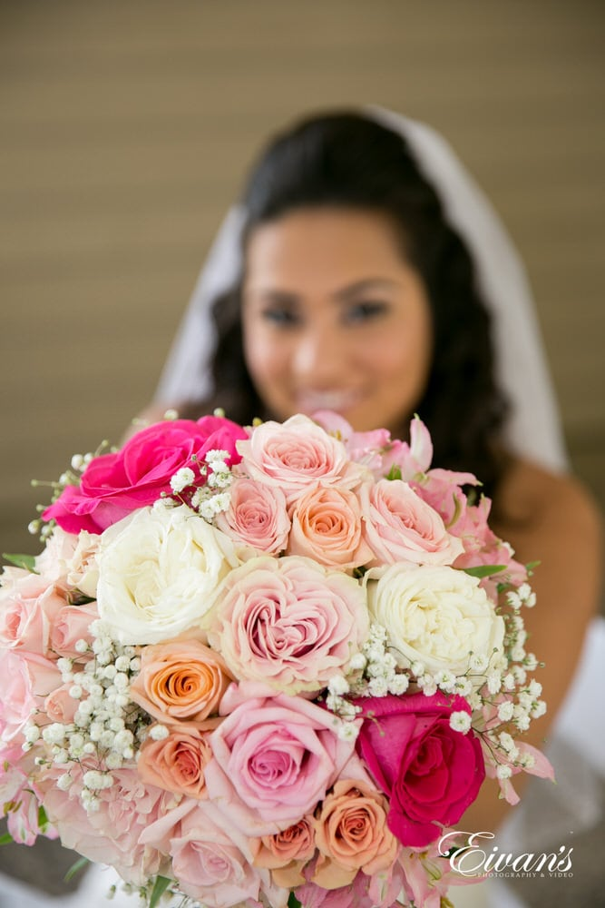 The bride holds up her beautiful bouquet filled with different colors of roses.