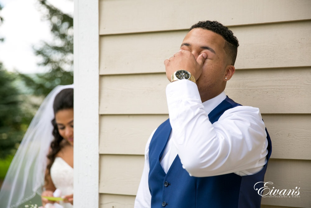 The groom begins to tear up and cry from the note his bride writes to him.