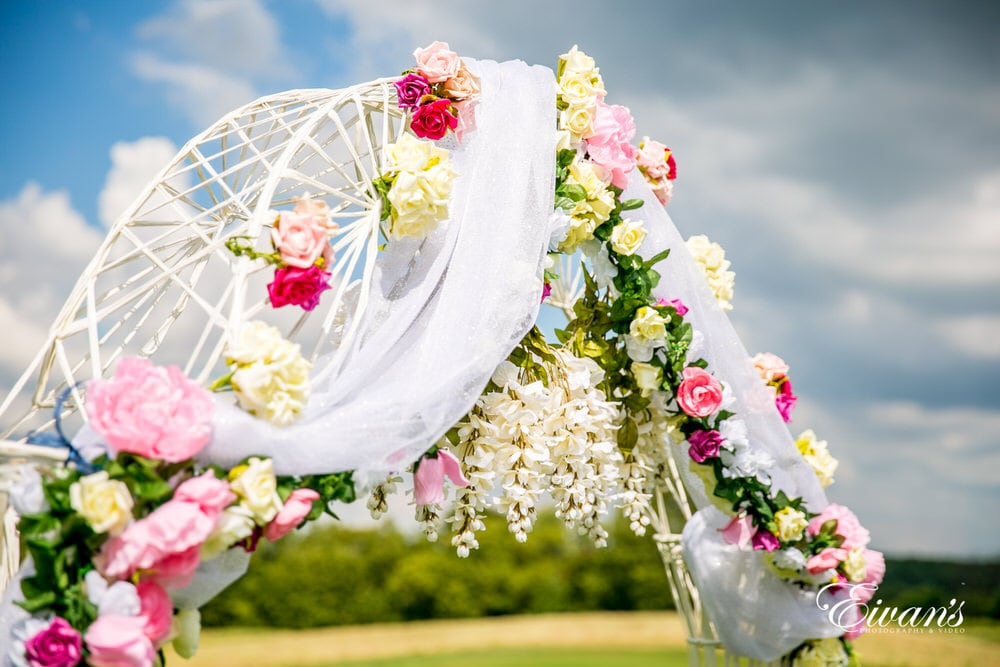 The archway that is set over the couple's beautiful kiss is covered in pink and white roses.