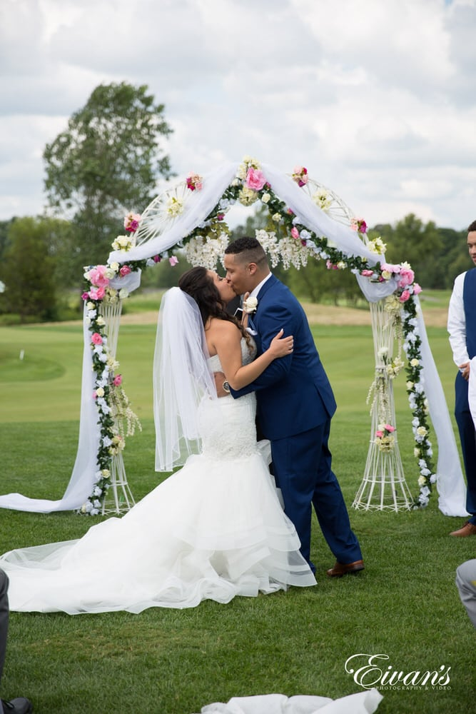 The bride and groom kiss in front of all their friends and family showing just how much they love one another.