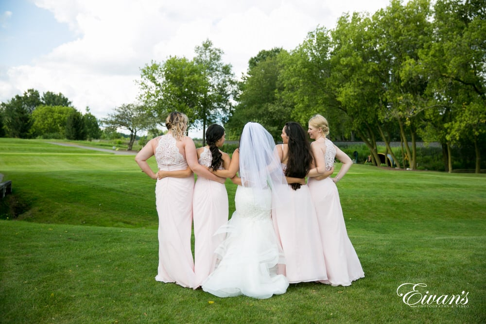 The bride and her bridesmaids stand on the golf course together celebrating this marriage.
