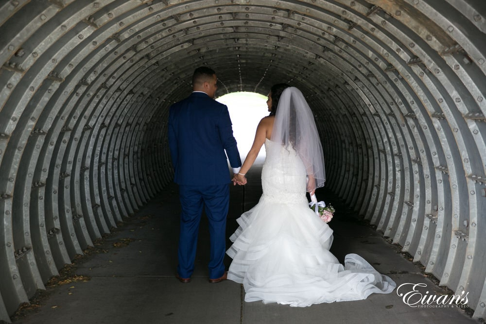 The groom and bride walk hand-in-hand with one another walking under a stunning archway.