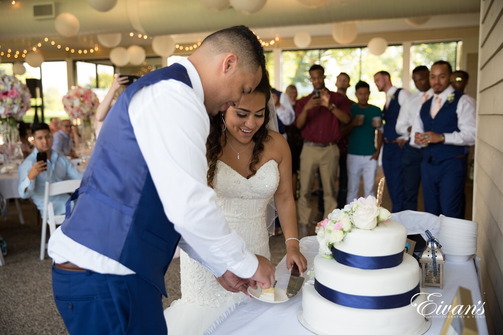 The bride and groom cut their cake in the process of making an amazing reception.