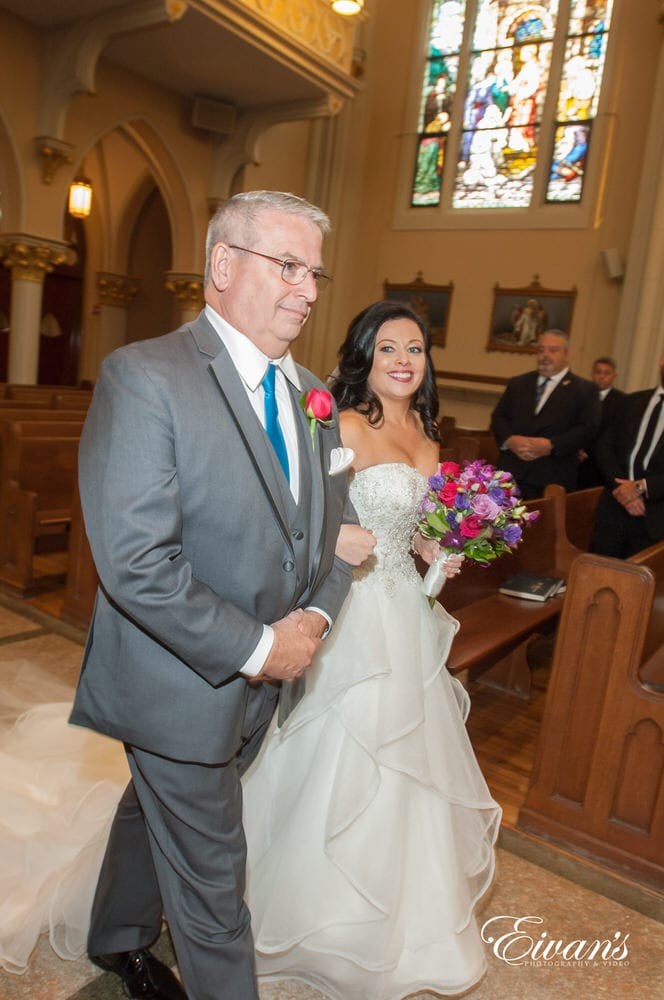 The bride is walked down the isle by her loving father on this particularly special couple.