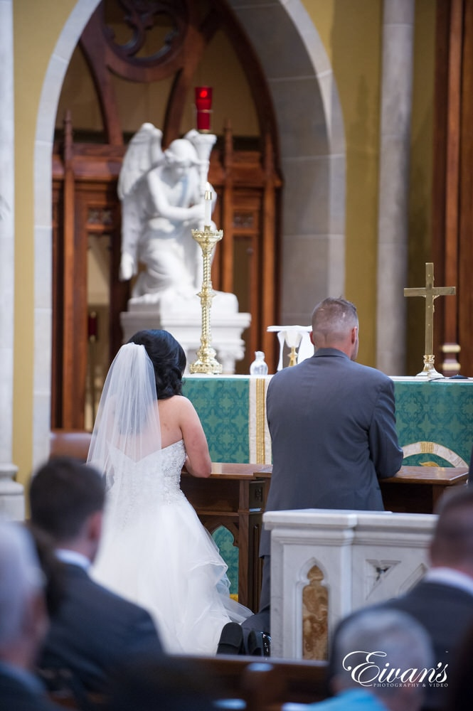 The couple kneel finally solidifying their vows together at the start of their new life.