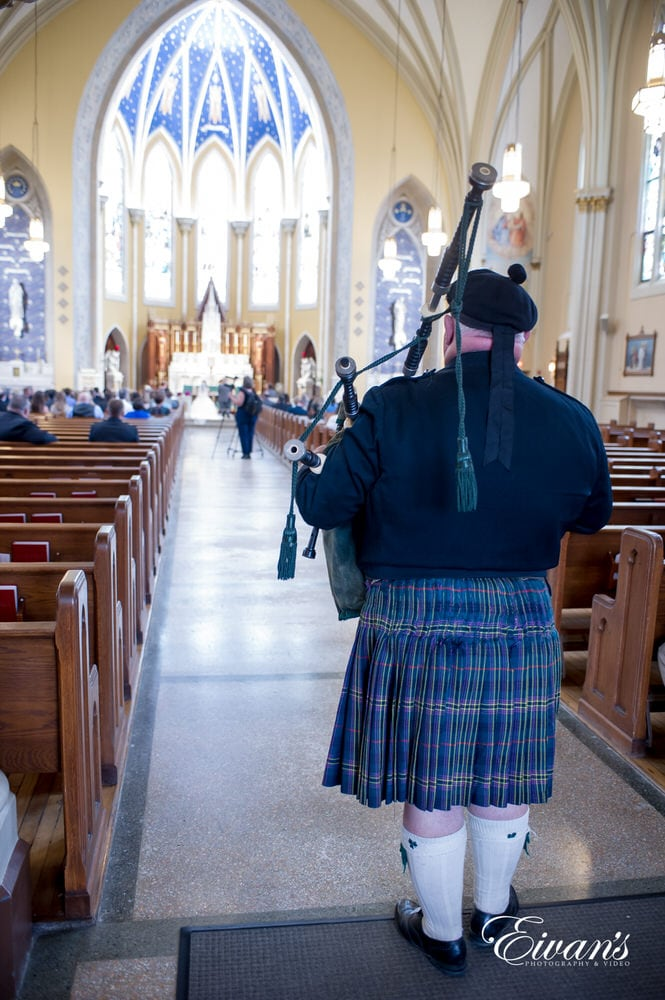 The bagpiper helps adjust the couple's leaving of their amazing ceremony.