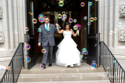 The couple smiles and gleams while they walk out of the chapel while bubbles are being blown at them.