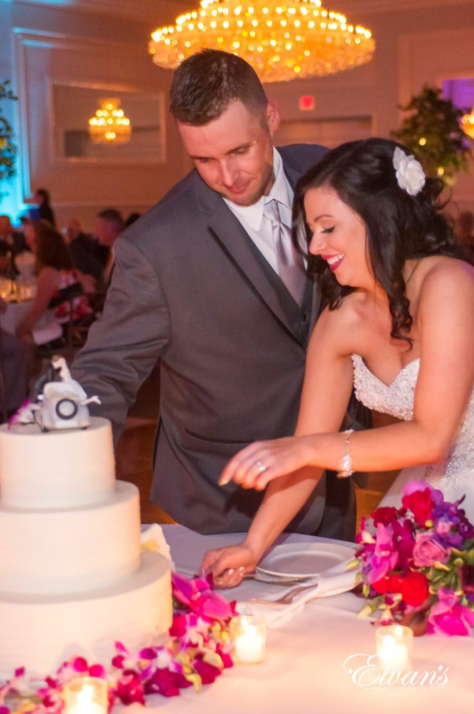 The couple cuts the cake together at such a fabulous reception party.