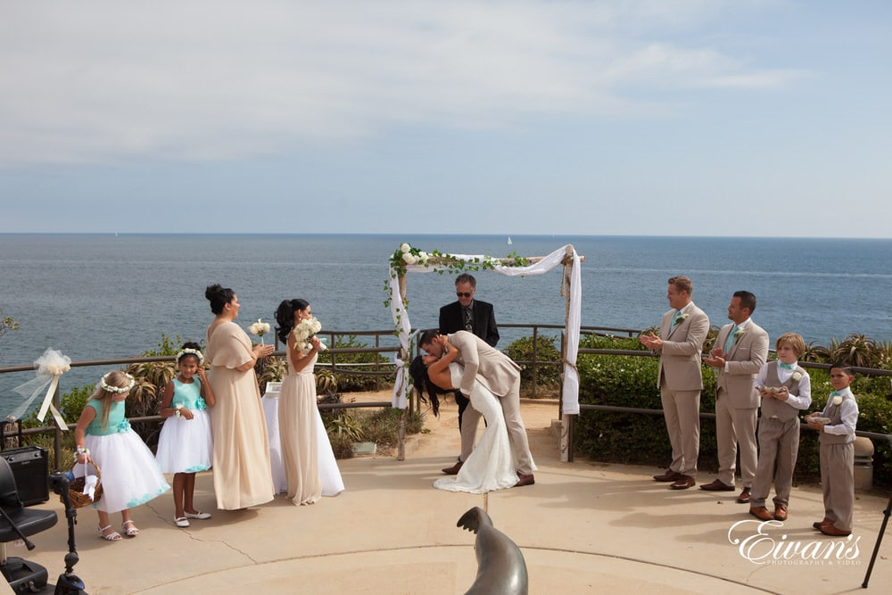The groom dips his bride as they kiss for the first time as a married couple.