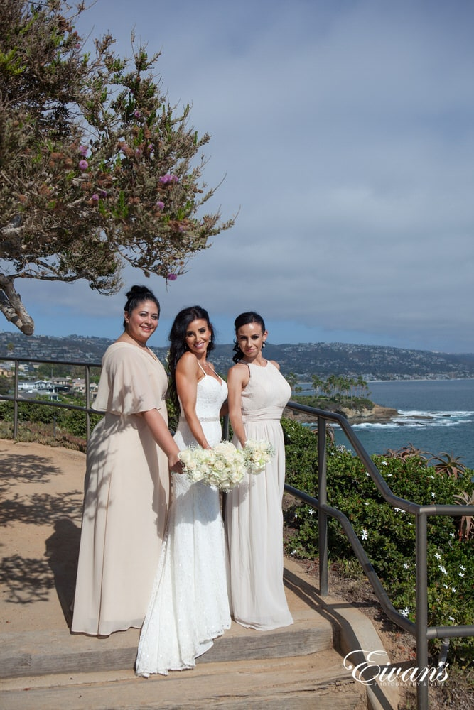 The bride and her bridesmaids stand on a set of stairs overlooking the sparkling ocean.