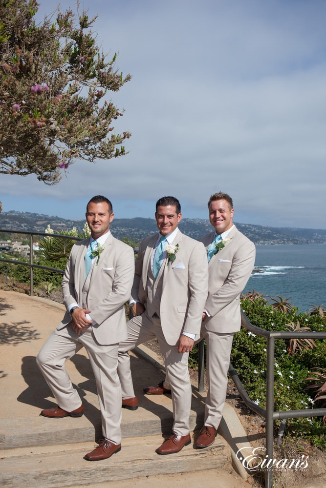 The groom and his groomsmen stand among a set of elegant stairs that set them onto of the world.