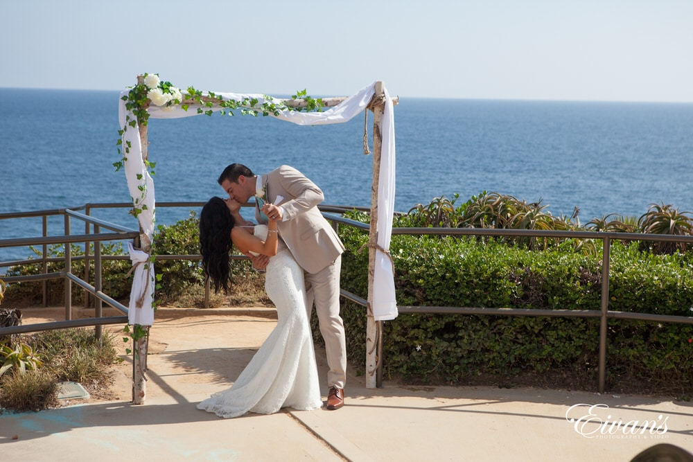 The bride and groom kiss under a stunning archway together kissing and celebrating their love.