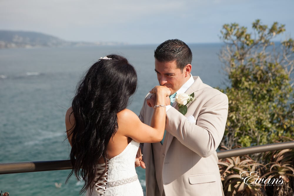 The groom kisses his gorgeous bride's hand showing chivalry is not dead.