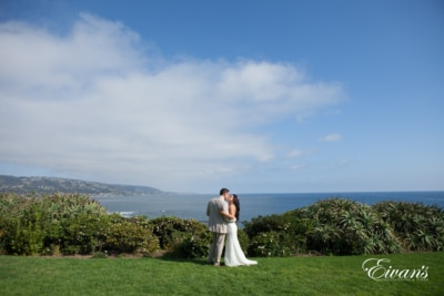 The bride and groom gaze over the beautiful hills into the dazzling blue ocean with all the promise of the world at their fingertips.