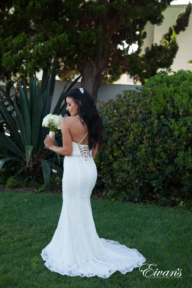 The bride stands looking truly stunning in her beautiful gown while being surrounded rich lush greens.