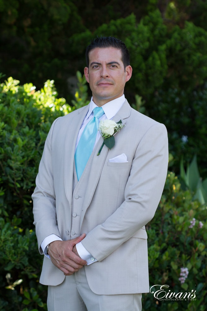 The groom stands very tall, looking extremely handsome in his special suit and tie for this particular occasion.
