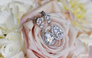 The bride's stunning jewelry effortlessly lays upon a light pink rose that is in her beautiful bouquet.