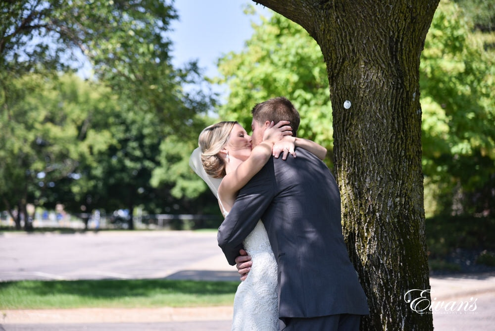 The couple kiss after seeing one another for the first time on this loving day.