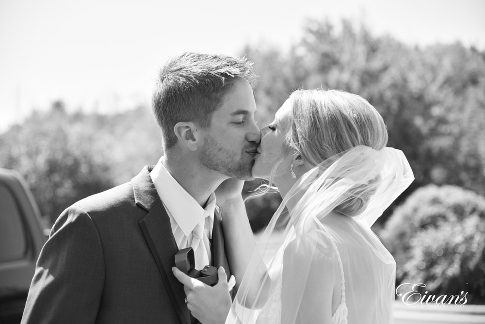 The bride and groom kiss after giving gifts to one another showing how much love one another.