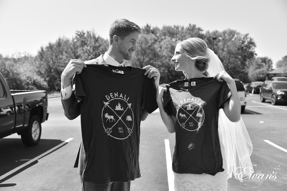 The bride and groom hold up their matching shirts as a part of their gifts to one another.