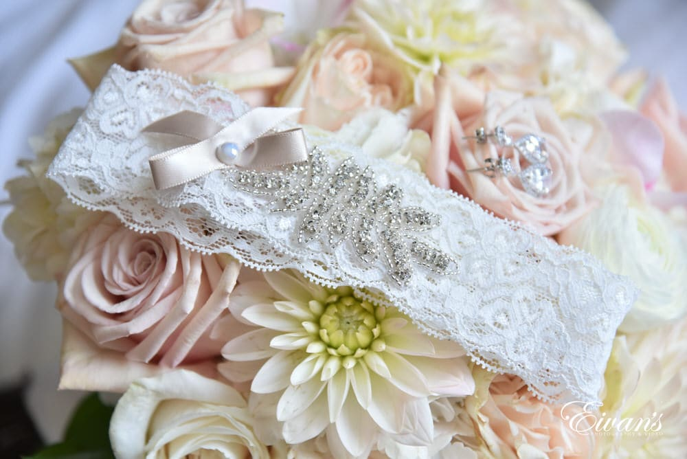 the bride's garter lays on top of the bride's gorgeous bouquet.
