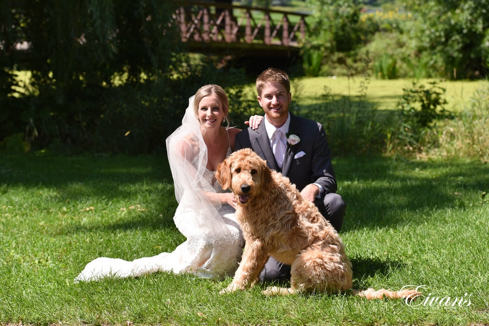The bride and groom lay with their four-legged friend.