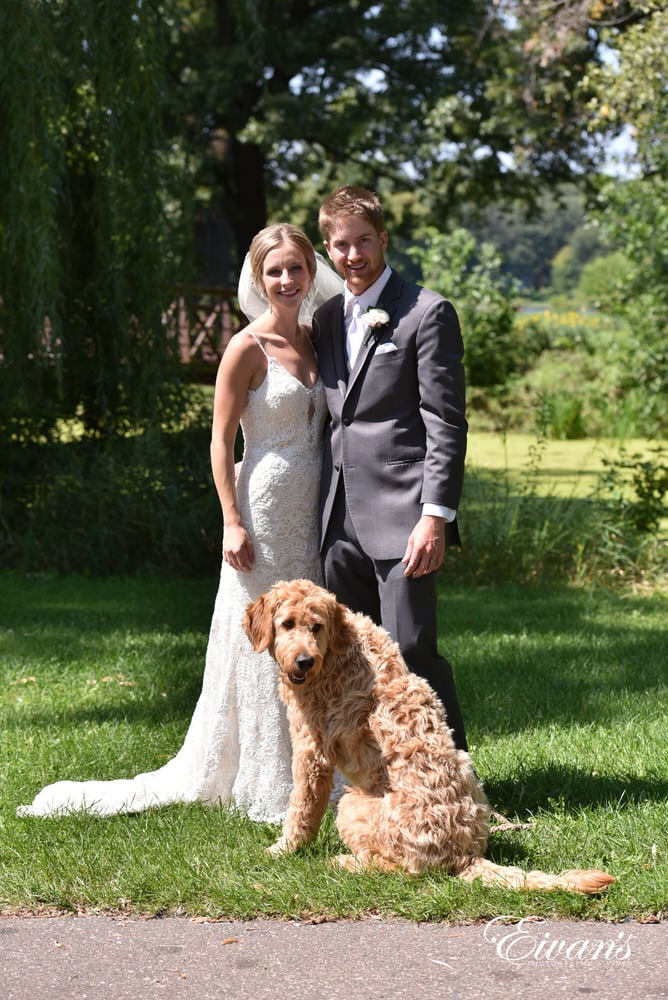 The gorgeous couple stand with their furry best friend in a beautiful green meadow.