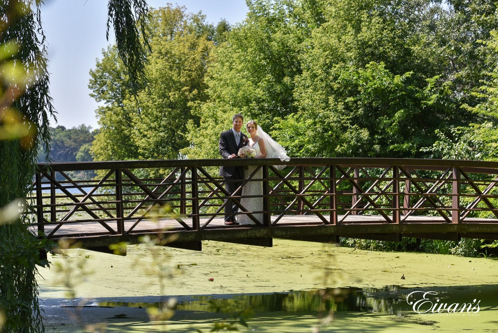 The groom and bride stand so effortlessly in an amazing scene of lush greens and on a rustic bridge.