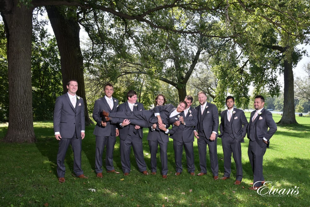The groom is held by all his groomsmen as he is being carried into his new lifestyle.