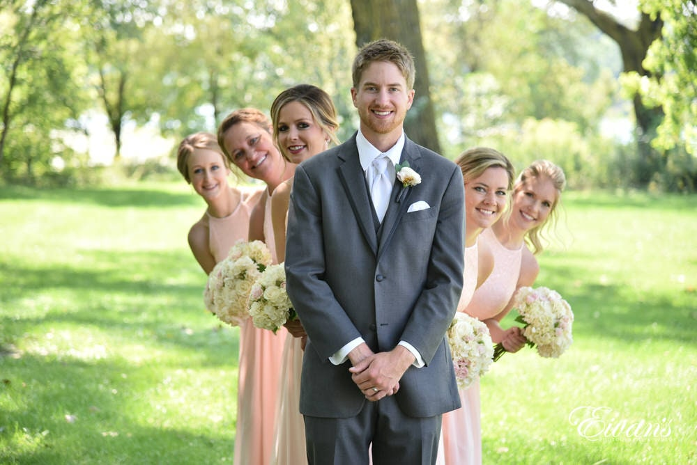 The groom stands in front of his bride's bridesmaids smiling about this joyous event.