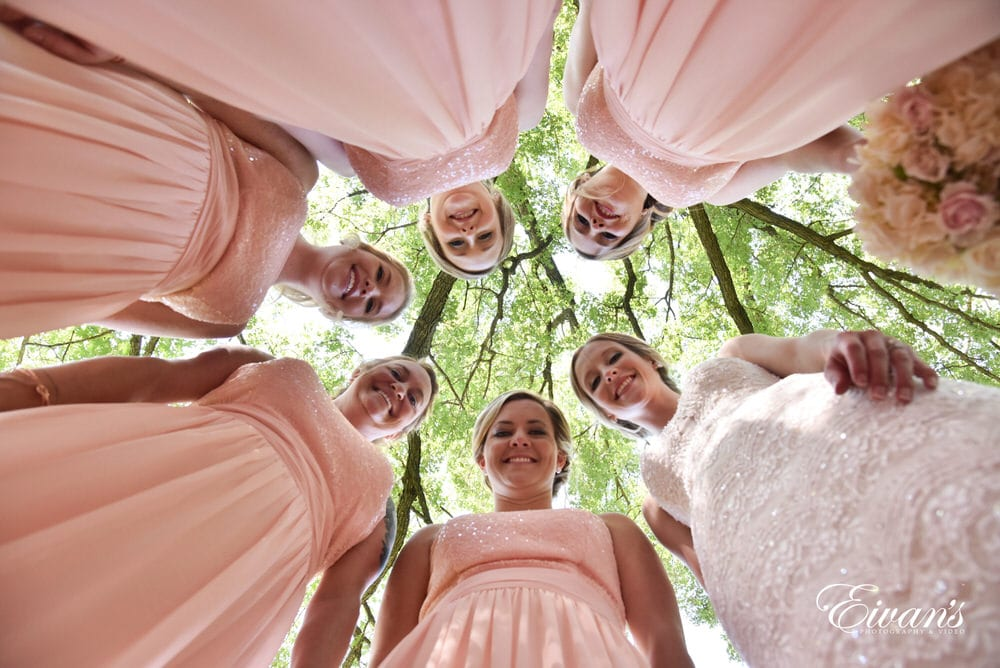 The bridesmaids and bride stand smiling and beaming with only true happiness.