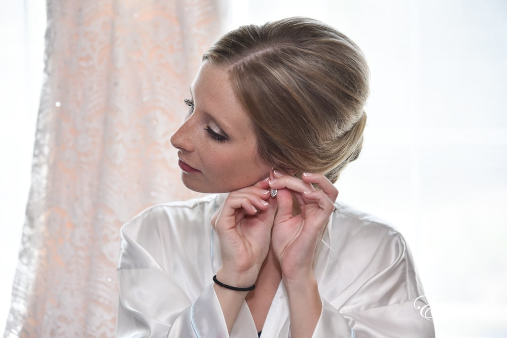 The bride puts on her dazzling jewelry preparing for her perfect day.