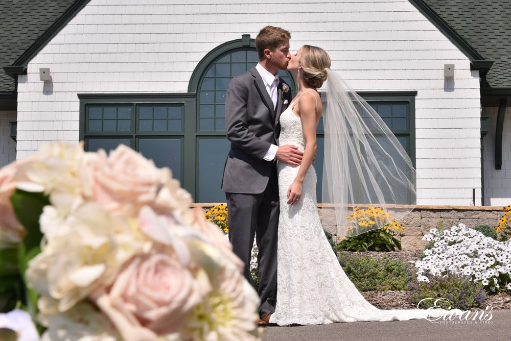 the bride and groom kiss standing at their beautiful venue falling in love all over again.
