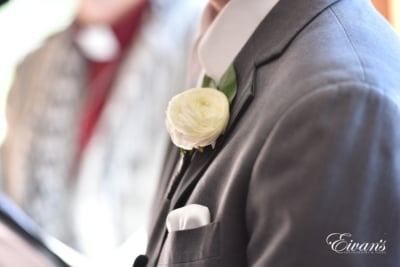 The groom's boutonniere is a white rose that fits onto his slate grey suit so well.