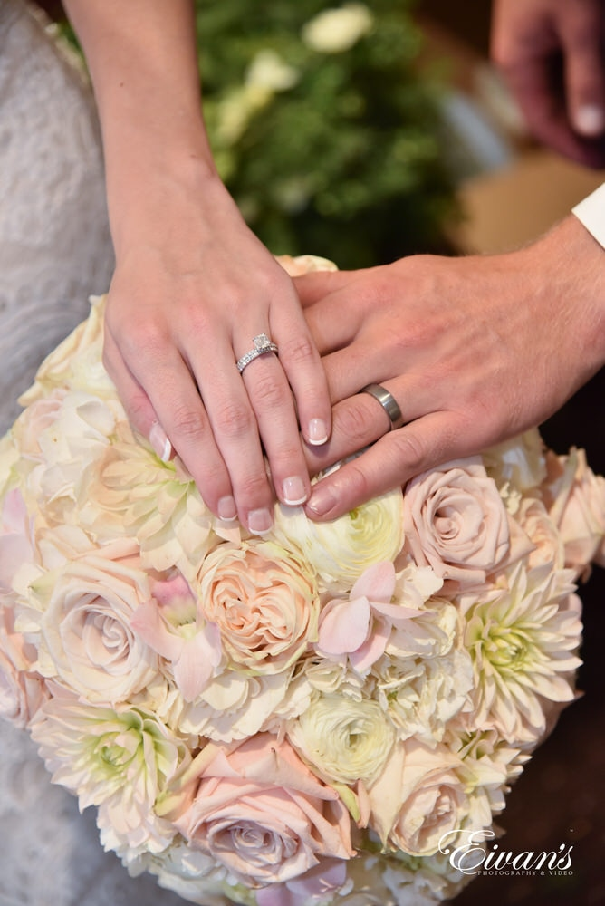 The bride and groom show off their rings on top of her amazing bouquet.