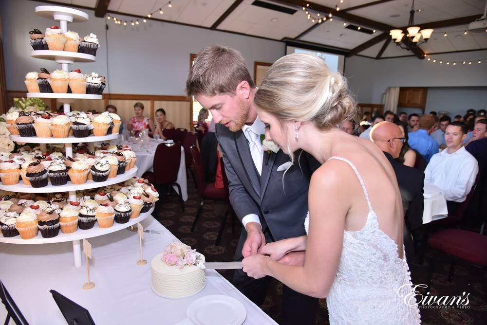 The bride and groom cut the cake in front of all their friends and family.