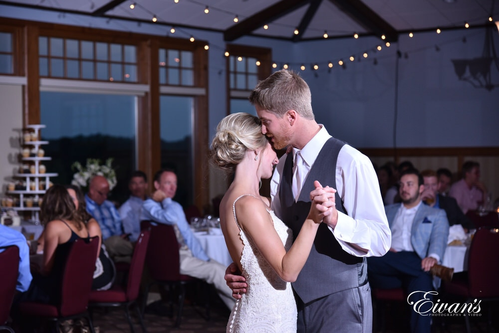 The groom whispers into the bride's ear telling her just how happy he is to be set with her for the rest of her life.