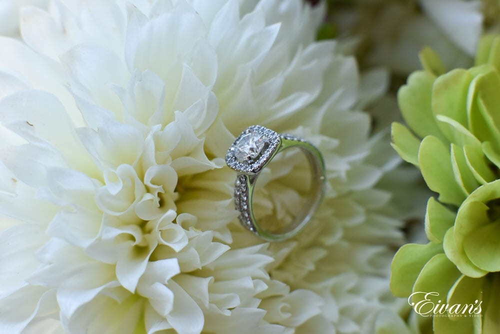 The bride's wedding ring in placed among the flowers in her bouquet that she will soon carry down the isle.