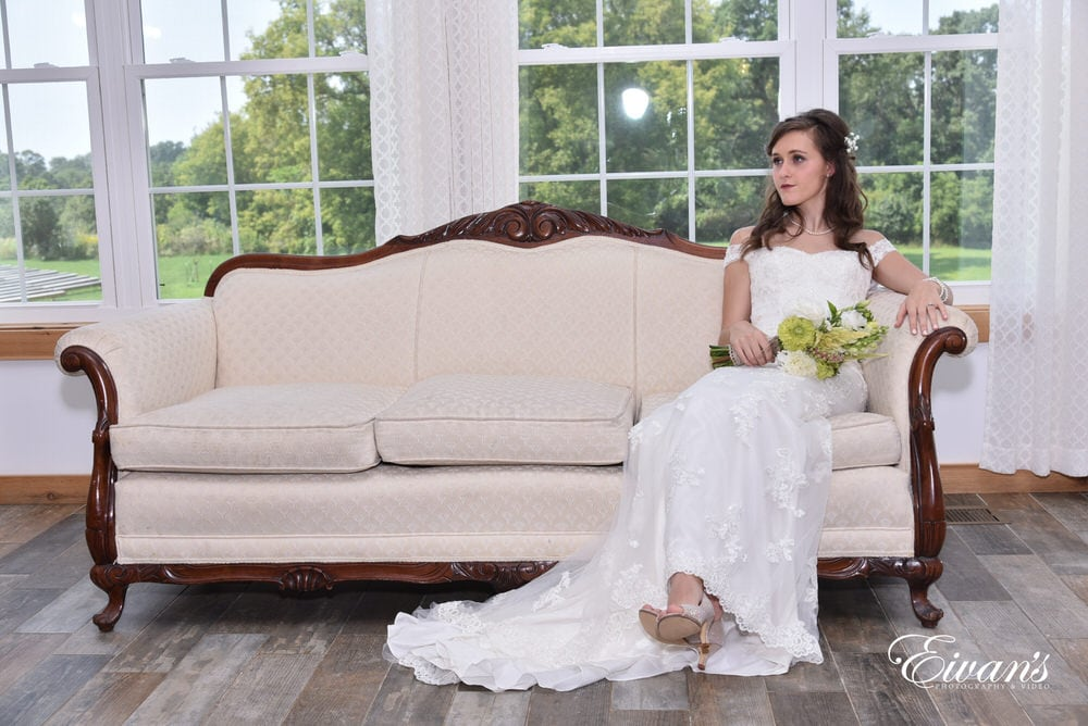 The bride sits effortlessly upon a beautiful white couch awaiting her walk down the alter.