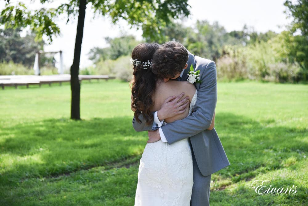The bride and groom hug while they both get to see one another for the first time on this joyous occasion.